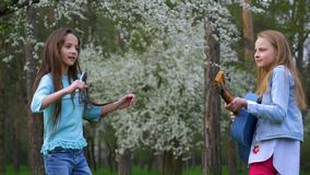 Children girl fools around sing songs and dancing together playing guitar. have fun in the spring woodland stock video