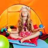 Children girl inside camping tent relax yoga stock photo