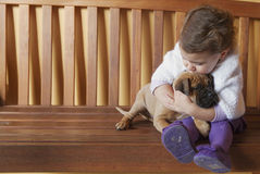 Children girl kissing and hugging her dog puppy Royalty Free Stock Photography