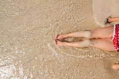 Children girl legs in beach sand shore Stock Images