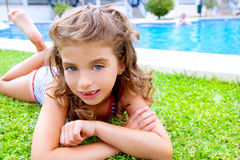 Children girl lying on pool grass in summer Stock Photo
