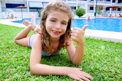 Children girl lying on pool grass in summer Royalty Free Stock Photo