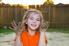 Children girl playing with mud sand ball and dirty hands. Smiling happy Royalty Free Stock Photography