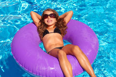Children girl relaxed on purple inflatable pool ring. Bikini children girl with sunglasses relaxed on purple inflatable pool ring Stock Photography