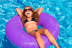 Children girl relaxed on purple inflatable pool ring Royalty Free Stock Photos