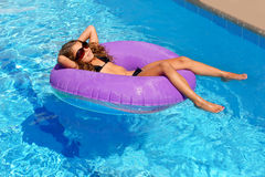 Children girl relaxed on purple inflatable pool ring Stock Photos
