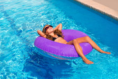 Children girl relaxed on purple inflatable pool ring Stock Photo