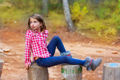 Children girl relaxed on a tree trunk. In the forest outdoor stock images