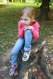 Children girl relaxed on a tree trunk Stock Photo