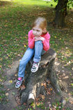 Children girl relaxed on a tree trunk Royalty Free Stock Photography