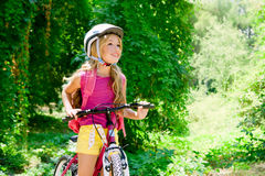 Children girl riding bicycle outdoor in forest royalty free stock photography