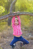 Children girl swinging in a trunk in pine forest. Children girl swinging in a tree trunk in a pine forest stock photo