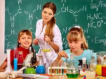 Children girl and teacher holding flask in chemistry class. Royalty Free Stock Photo
