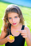 Children girl testing love with daisy flower. Blue eyes children girl testing love with yellow daisy flower petals royalty free stock image