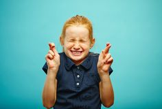 Children girl tightly closed his eyes and put fingers crossed, make a wish, believe in the dream, expresses heartfelt. Emotions, has funny facial features stock photography