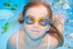 Children girl underwater goggles swimming. Children girl with goggles swimming underwater around fishes Royalty Free Stock Photos