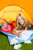 Children girl writing notebook in camping tent. Children girl writing a notebook in camping tent with flowers Stock Image
