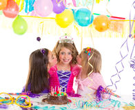 Children girls group in birthday party greetings with a kiss. With candle cake stock photography