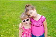 Children girls hug in green grass park Royalty Free Stock Photo