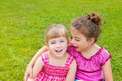 Children girls hug in green grass park Stock Photo
