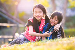 Children girls hug in green grass park stock image