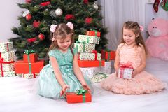 Children girls look gifts under a Christmas tree. Children girls look box of gifts under a Christmas tree Stock Image