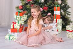 Children girls  look gifts under a Christmas tree. Children girls look box of gifts under a Christmas tree Royalty Free Stock Photos