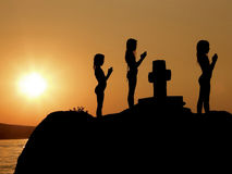 Children, girls in prayer on sunset. Sisters in prayer on the stone with cross Stock Photography
