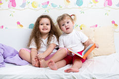Children girls read book in bed. Kids sisters reading a book in bed Royalty Free Stock Photo