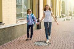 Children teens go to school holding hands. Children- girls teens, go to school holding hands stock images