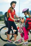 Children girls wearing helmet children repair bicycle. Stock Images