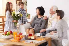 Children giving flowers to grandparents royalty free stock photo