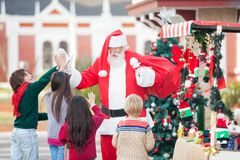 Children Giving High Five To Santa Claus Royalty Free Stock Photos