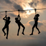 Children gliding on the flying fox contraption against a blue cl Stock Photo