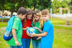 Children with a globe are learning geography Royalty Free Stock Photography