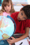Children with a globe stock images
