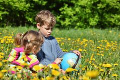 Children with globe sit on meadow Stock Photos