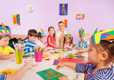 Children glue paper crafts together with teacher. Group of children boys and girls with teacher making crafts with paper and glue sitting by the table in class Royalty Free Stock Photos