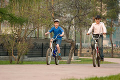 Children go for a drive on bicycles on park. Royalty Free Stock Image