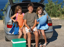 Children go on summer vacation. Children (best friends) with fins, mattresses, portable fridge and accessories for fishing, sitting in the car, ready to go on Stock Photography