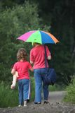 Children go for walk with umbrella, rear view Stock Photography