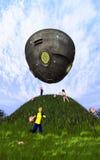 Children of the Gods. Children play beneath a strange UFO hovering over a grassy hill Stock Illustration