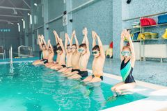 Children with goggles and flippers sits near pool. Hands raised. Kids ready to jump in water. Happy kids in modern sport center. Concept of fun, leisure and Stock Photo