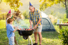Children and grandfather having a barbecue party Stock Photos