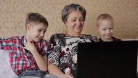 Children and grandmother with laptop. Family grandmother and two grandchildren are sitting on the couch with a laptop and playing computer games stock video footage
