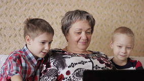 Children and grandmother with laptop stock video