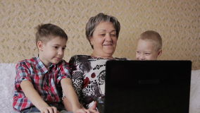 Children and grandmother with laptop stock video footage