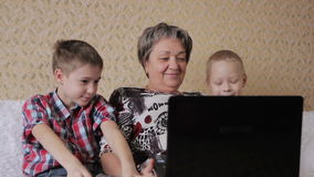 Children and grandmother with laptop stock footage