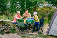 Children with grandmother at a picnic with a tent stock photo