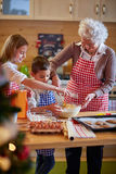 Children and grandmother preparing Xmas cookies. Family time Royalty Free Stock Images